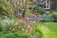 Seating area in cottage garden. Border planting includes Aquilegia and Geum 'Red Wings'
