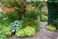 Arched gateway through a red brick wall toward the island bed with Hakonechloa, Verbena bonariensis and grasses. Hosta 'Striptease' and Hosta 'Captain Kirk'