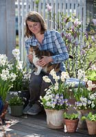 Woman and pet cat on terrace with spring containers