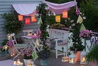 Balcony with pink awnings, lanterns and columns from Mandevilla 'Rio White' and 'Rio Pink'