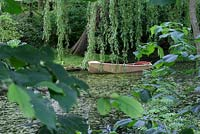 View from the woodland walk of an old wooden rowing boat in the pond, shaded by a weeping willow tree - Sallowfield Cottage B&B, Norfolk