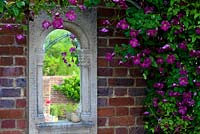 Mullion style mirror on brick wall with clematis