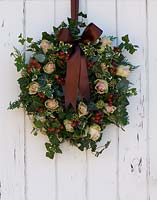 Christmas wreath hanging on white painted wooden door. Including Rosa 'La Belle', Hypericum 'Coco Rio', Ivy and variegated Euonymus.