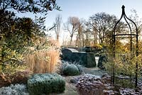 Formal garden in winter with Sedum, Calamagrostis acutiflora, clipped Box, Olea and yorkstone paths - Winfield House