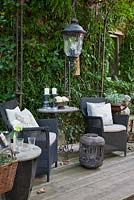 Modern styled black wicker chairs with white linen cushions on a wooden deck. Table with candle holders, a lantern and other decorative metal objects against a backdrop of Hedera helix