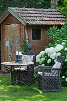 In a shaded garden next to summerhouse, a rest area with two wicker armchairs with cushions and a bistro table. White flowering Hydrangea arborescens 'Annabelle'