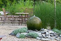 Water feature made of granite sphere and shingles. Metal garden furniture with bistro table next to dry stone wall. Artemisia schmidtiana 'Nana' and Miscanthus sinensis