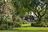 A Bavarian country garden with lawn, old fruit trees, climbing roses and perennial borders