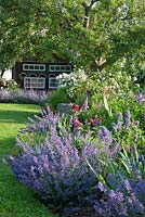 Bavarian country garden with perennial borders, roses and a bee house sheltered under old fruit trees