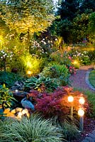 Mixed summer borders with spot lights at dusk