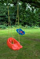 Childrens' novelty swing seats, suspended from bough of tree - Furze House NGS, Rushall, Norfolk