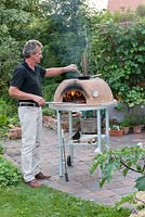 Man using an outdoor pizza oven