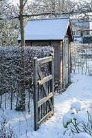 Garden gate and summer house in snow
