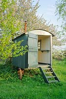 Shepherds hut in wild garden with Prunus avium, wild cherry, behind - The Mill House, Little Sampford, Essex