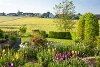 The view is from a rural garden with clipped hornbeam arch and hedges to flowering meadows and a small village. Plants include Paeonia suffruticosa 'Kouka Mon' and Iris germanica