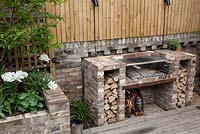 Barbecue with cut logs on decked patio area