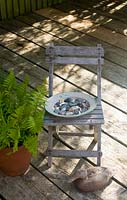 Childs chair with plate of pebbles on wooden decking patio