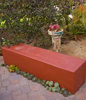 Bench underplanted with succulents. Plants include Echeveria agavoides 'Lipstick', Echeveriia imbricata, Sempervivum 'More Honey' and Kalanchoe thyrisiflora
