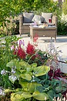Seating on terrace with planting of  Astilbe, Hosta, Ligularia and Primula vialii