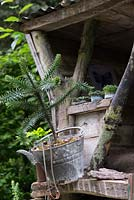 The NSPCC Garden of Magical Childhood - treehouse with a young pine tree in a galvanised bucket and a catapult