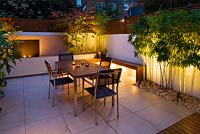 Minimalist Garden lit up at night - Acer Aconitfolium, table and chairs and Phyllostachys Aurea and water feature