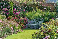 View of a walled rose garden with seat.