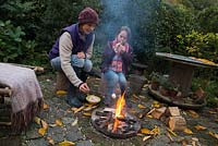 Mother and daughter roasting marshmallows over a firepit in an autumnal back garden.