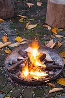 A firepit alight in an autumnal back garden