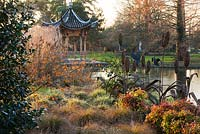 Evening view across the lake at Seven Acres to the Chinese pagoda with Hamamelis Aphrodite, Carex Flagellifera and Carex Ashimensis evergold, winter. RHS Garden, Wisley.