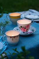 Vintage teacups used as tealight holders on a garden table