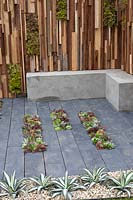 Slate paving, drought tolerant planting and living fencing with vertical planting in 'The Austerity Garden'