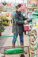Woman at a garden centre selecting compost and adding to trolley