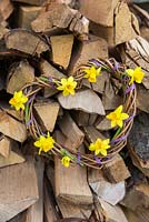 Woven daffodil wreath against stack of logs. Narcissus 'Tete a tete'