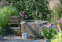 Stone trough water feature, chair and mixed planting including Malva moschata, Phlox 'Laura' and Nepeta