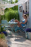 Woman relaxing in nautically themed garden