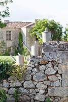 Old watering cans on stone wall of chateau in France (Chateau Rigaud)