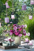 Display of Cosmea, dahlias and small rose hips with lanterns hanging from tree