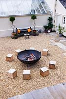Gravel seating area with large square wooden blocks for seats and fire cauldron