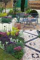 Seating area with mosaic surfaces and colourful flowerbeds -