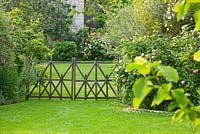 Lawn and a decorative wooden fence by Stephane Cassine. Les Jardins de Roquelin, Loire Valley, France