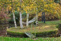 Hammock suspended from Betula Jermyns trees on island with wooden bridge - autumn