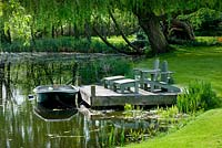 Decked terrace beside the lake with adirondack wooden chairs and boat