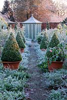 Path through the rose garden to a summerhouse with David Austin roses and terracotta containers with clipped buxus