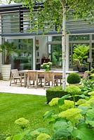 View across lawn and Hydrangea 'Annabelle' to dining area on limestone patio - The Glass House, Petersham - Architects Terry Farrell Partners - Garden design by Sallis Chandler