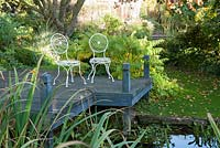 Chairs on decking beside pond with Rhus typhina 'Dissecta' - Windy Ridge