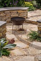 Crazy paving, rustic irregular slabs and circular dry stone wall with Purbeck stone top and barbeque, Halo, RHS Hampton Court Flower Show 2014