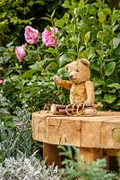 Old fashioned teddy bear and skipping rope on wooden bench, The NSPCC Legacy Garden, RHS Hampton Court Flower Show 2014