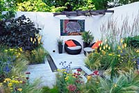 Hedgehog Street. Courtyard garden, contemporary chairs with cushions. Kniphofia, stipa, calamagrostis, achillea