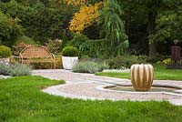 Gourd-shaped water fountain in gravel bed and brown metal lattice garden bench between two concrete planters with green velvet boxwood Buxus 'Green Velvet' shrubs and pink hydrangeas paniculata 'Quick Fire' in backyard garden in autumn. Il Etait Une Fois garden, Monteregie, Quebec, Canada.