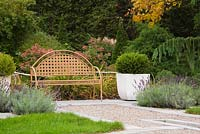 Brown metal lattice garden bench between two concrete planters with green velvet boxwood - Buxus 'Green Velvet' shrubs and pink hydrangeas paniculata 'Quick Fire' in back garden in autumn.